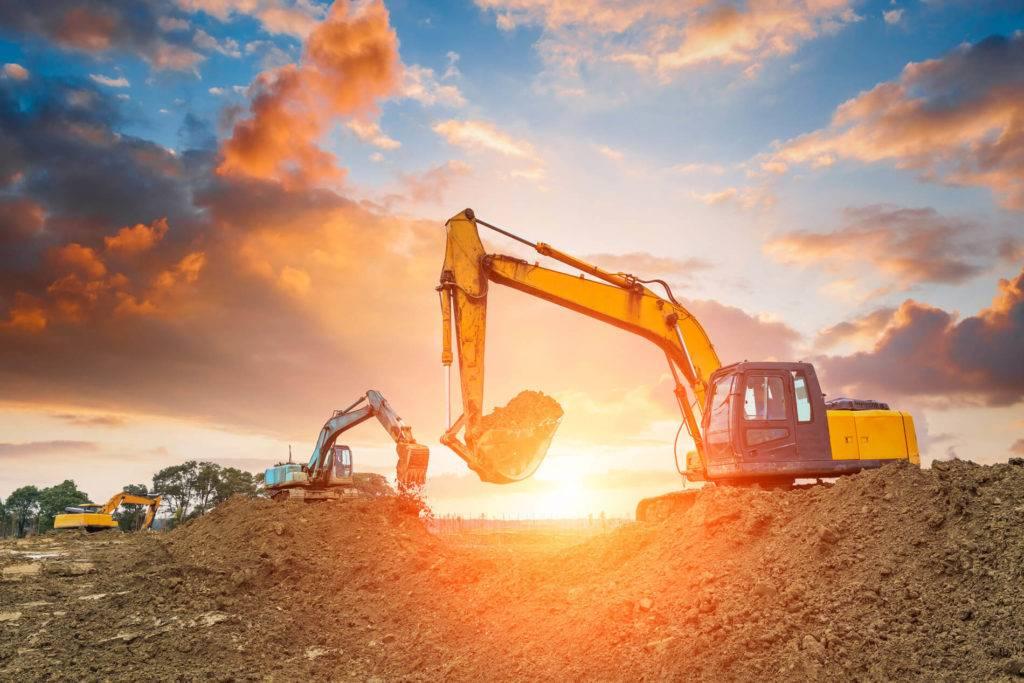 excavators at sunset